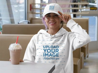 Hoodie Mockup Featuring a Woman at a Restaurant Wearing a Dad Hat 31189