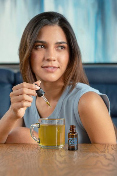 Dropper Mockup of a Young Woman Adding CBD Oil to Her Tea 32086