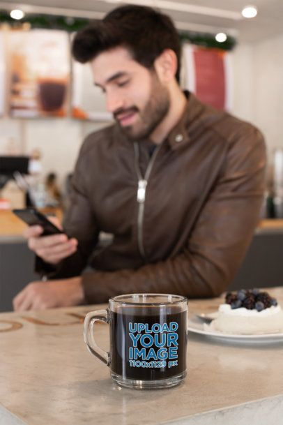 Clear Mug Mockup of a Bearded Man Using His Phone at a Cafe 31776