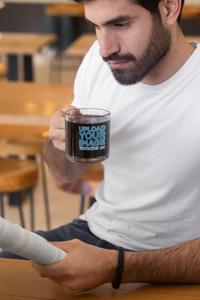 Mockup Featuring a Man Holding a Clear Glass Mug While Reading 31783