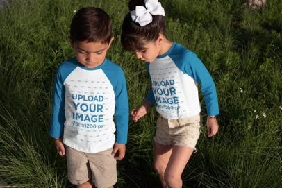 Raglan Tee Mockup Featuring Two Little Siblings Playing by the Grass 31673