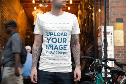 T-Shirt Mockup of a Tattooed Man Standing Next to a Bike 3352-el1