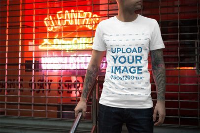 Mockup of a Man Wearing a T-Shirt Featuring Neon Signs in the Background 3353-el1