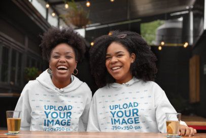 Hoodie Mockup of Two Women Laughing at a Bar 32298