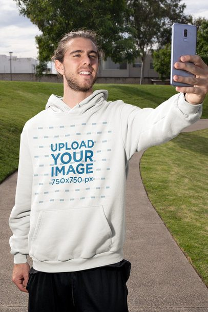 Mockup of a Man with a Hoodie Taking a Selfie on the Street 32312