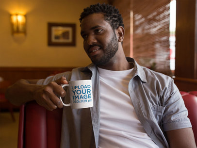 Young Man Having a Conversation and Holding a Mug Mockup a12323