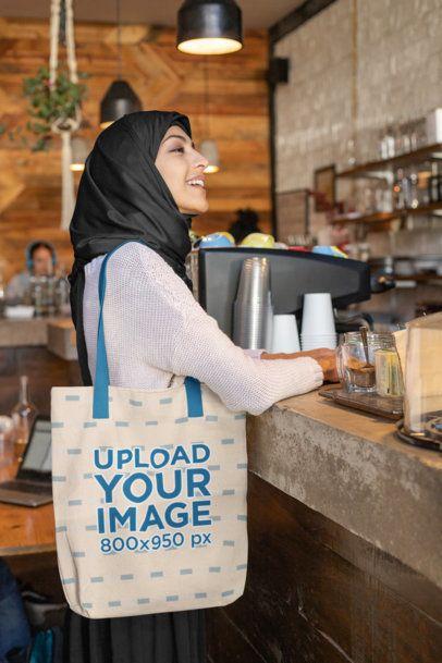 Tote Bag Mockup of a Woman Wearing a Hijab at a Cafe 32395