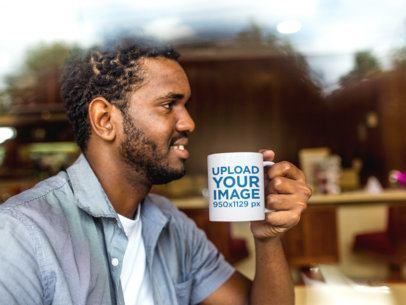 Young Man at a Coffee Shop Holding His Mug Mockup a12325