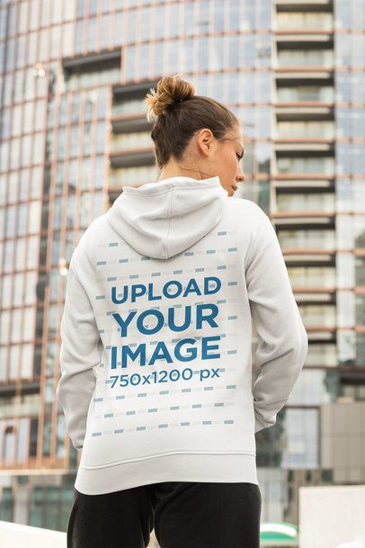 Hoodie Mockup of a Woman in an Athleisure Look on a Street with Skyscrapers 32448