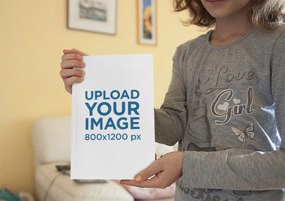 Mockup of a Little Girl Showing the Cover of a Book 3444-el1