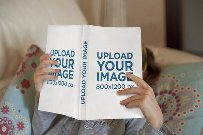 Mockup of a Girl Reading a Paperback Book at Home 3446-el1
