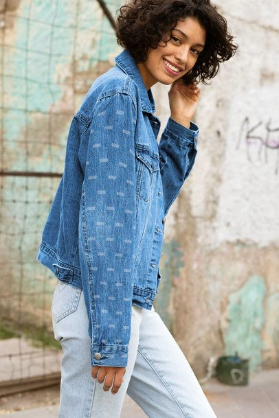 Denim Jacket Mockup Featuring a Short-Haired Woman Posing by an Old Wall 32567