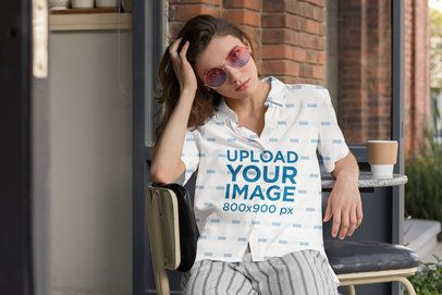 Button up Shirt Mockup Featuring a Woman Sitting on a Chair Outside a Cafe 33135