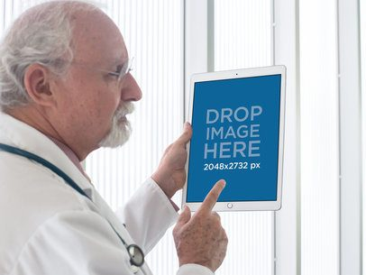 Mockup of a Senior Male Physician Showing an iPad in Portrait Position 12440b