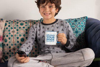 Mockup of a Boy Holding an 11 oz Colored Rim Mug While Watching TV 33167