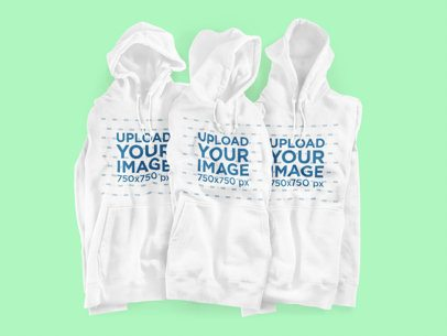 Mockup of Three Hoodies Placed on a Customizable Surface 3590-el1