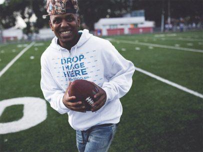 Smiling Young Black Man Playing Football Wearing a Hoodie Mockup b12450