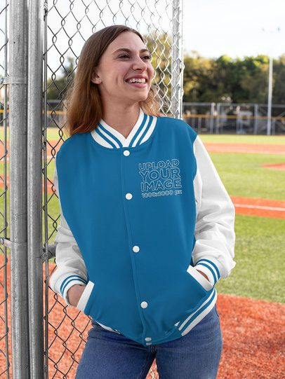 Mockup of a Happy Woman Wearing a Varsity Jacket Next to a Baseball Field 33200