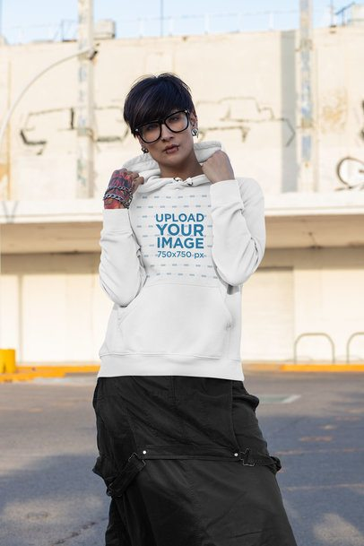 Hoodie Mockup Featuring a Woman with an Androgynous Look Posing on the Street 32935