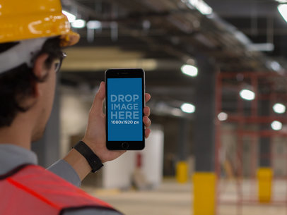 Mockup Featuring a Male Worker Staring at an iPhone Inside a Factory 12583