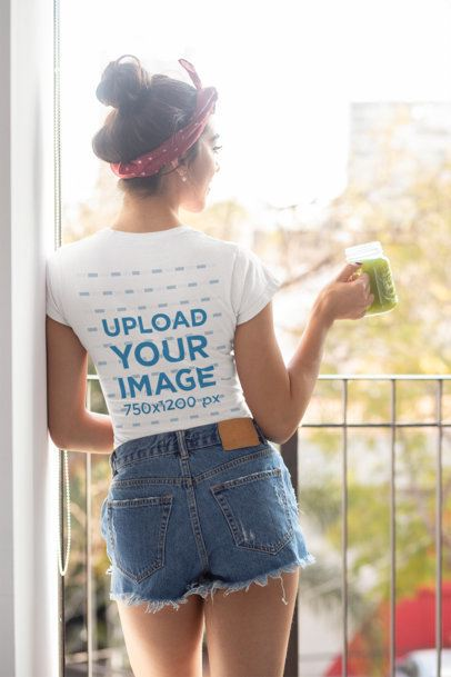 Back View T-Shirt Mockup of a Woman Holding a Healthy Smoothie at a Balcony 32750