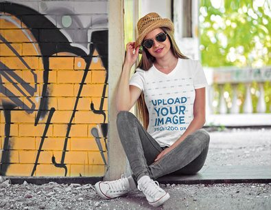 V-Neck T-Shirt Mockup Featuring a Woman Sitting by a Graffitied Wall 3682-el1