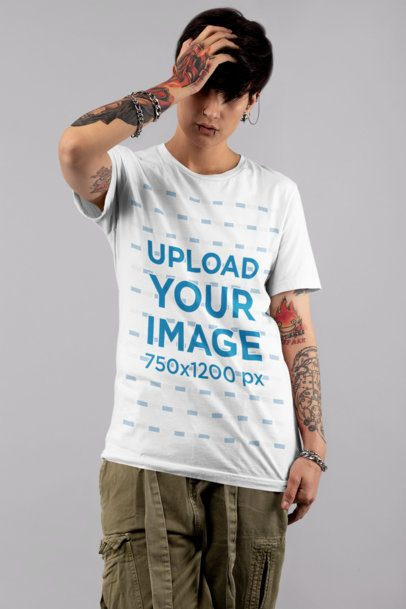 T-Shirt Mockup of an Androgynous Woman with Tattooed Arms at a Studio 32929