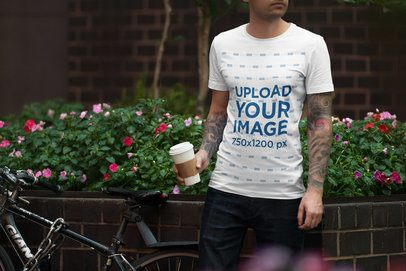 T-Shirt Mockup Featuring a Tattooed Man Holding a Man Posing by a Planter With Flowers 1956-el1
