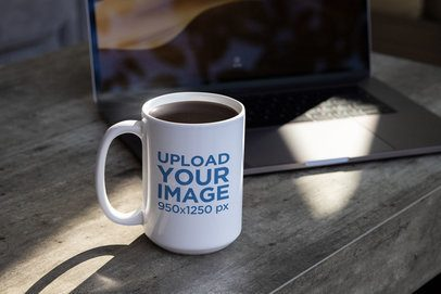 Mockup of a Sticker on a Coffee Mug Beside a Laptop 33600