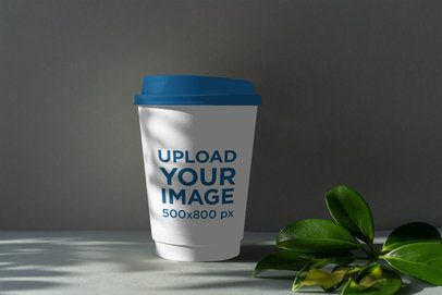 Mockup Featuring a Coffee Cup With a Colored Lid Placed by Some Leaves 3764-el1
