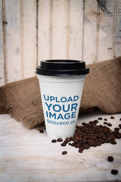 Mockup of a Customizable Paper Cup Placed by Some Coffee Beans 3752-el1