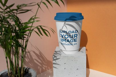 Mockup of a Coffee Cup Featuring a Plant and a Cement Block 3769-el1