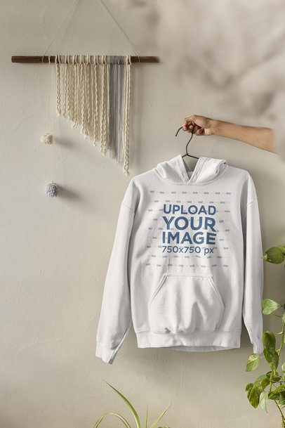 Mockup Featuring a Woman's Hand Holding a Pullover Hoodie by a White Wall 33733
