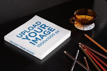 Mockup of a Square Paperback Book Placed on a Dark Surface by Some Colored Pencils 33908