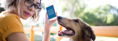 Young Trendy Girl Holding an iPhone 6 Mockup in Vertical Position with her Dog Outdoors a12794wide