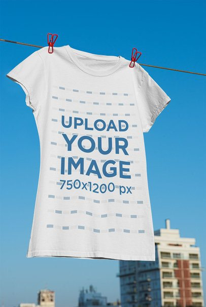 Mockup of a Women's T-Shirt Hanging on a Line with an Urban Background 33732