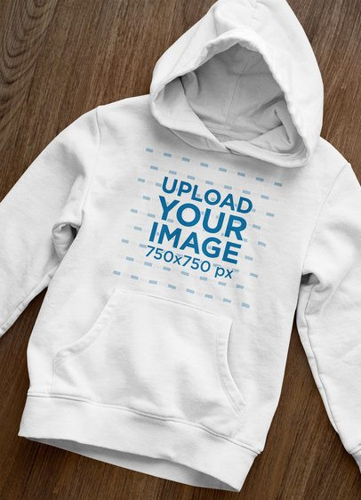Front-View Mockup of a Pullover Hoodie Laid over a Wooden Surface 33871