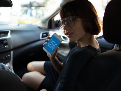 Lovely Girl Riding in the Frontseat of a Car Holding an iPhone 7 in Portrait Position Mockup a12942wide