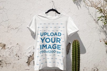 Mockup of a T-Shirt Hanging on a White Wall by Some plants 33868