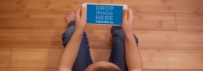 Mockup Featuring a Girl Holding an iPhone While Sitting on Wooden Floor 12998wide