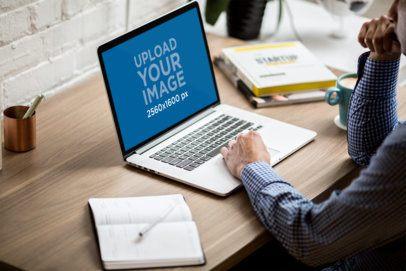 MacBook Mockup of a Man Working at a Desk 3833-el1