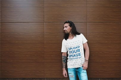 Mockup of a Man with Tattoos Wearing a Basic Tee by a Wooden Wall 34114-r-el2