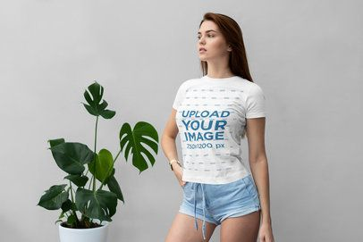 Mockup of a Serious Woman Wearing a T-Shirt and Posing by a Tropical Plant 4288-el1