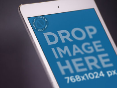 White iPad Mini Closeup Mockup in Angled Portrait Position Over a Dark Background a12758