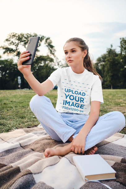 Mockup of a Teenager with a T-Shirt Taking a Selfie at the Park 34490-r-el2