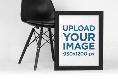 Mockup of a Framed Art Print Leaning Against a Dark Modern Chair 4474-el1