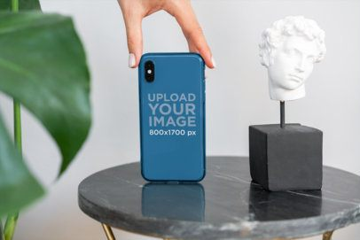Mockup of a Woman Holding a Clear Phone Case Next to an Ornament 4642-el1