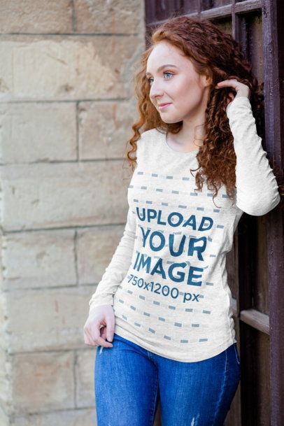 Mockup of a Woman Wearing a Heather Long Sleeve Tee and Posing by an Old Door 4729-el1