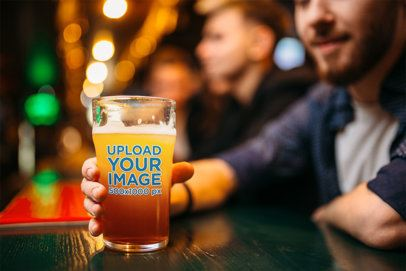 Mockup of a Man Holding a Beer Glass at a Bar 37322-r-el2
