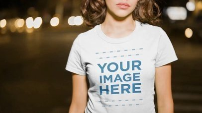 Mockup Video of a Beautiful Girl With Curly Hair Wearing a Round Neck T-Shirt in the City at Night a13542
